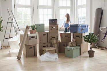Woman with cardboard boxes in new apartment looking out of window - RBF004732