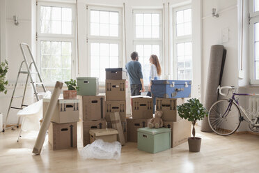 Couple with cardboard boxes in new apartment at the window - RBF004735