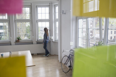 Woman in office looking out of window - RBF004738