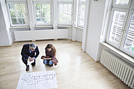 Real estate agent showing construction plan to client in empty apartment - RBF004744