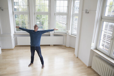 Happy man standing in empty apartment - RBF004747