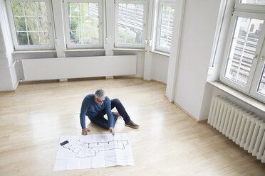 Man looking at construction plan in empty apartment - RBF004750
