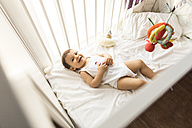 Portrait of happy baby boy lying in his cot - JASF000982