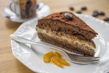 Piece of chocolate cake with orange marmalade on plate - PVCF000865