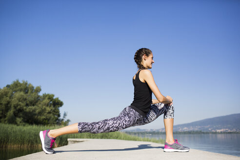 Young woman doing exercise on pier - MRAF000076