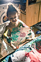Girl draws red picture with fingercolors and is fully smeared of colors - YNF000027
