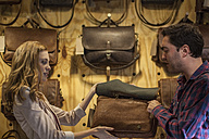 Man and woman looking at leather bag in shop - ZEF008933