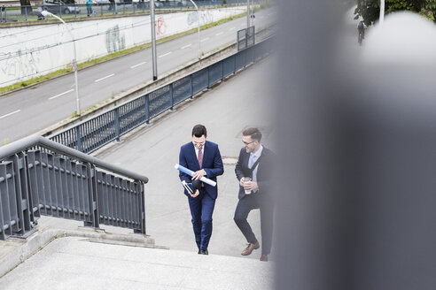 Two young businessmen walking together in the city - UUF007973