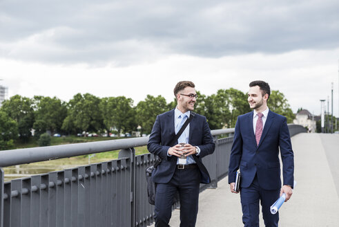 Two young businessmen walking together in the city - UUF007979
