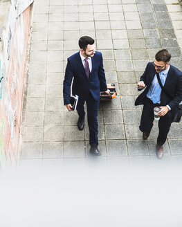 Businessmen on business trip walking with wheeled luggage - UUF007985