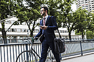 Businessman with bicycle walking in the city, using smart phone - UUF007994