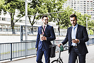Businessmen walking with bicycle in the city, talking - UUF008003