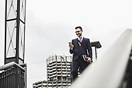 Young businessman standing at railing, using smart phone - UUF008009