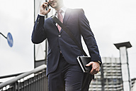 Young businessman standing at railing, using smart phone - UUF008012
