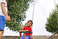 Portrait of happy little boy sitting on a swing - VABF000670