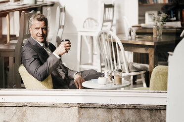 Businessman sitting in a cafe drinking coffee - KNSF000014