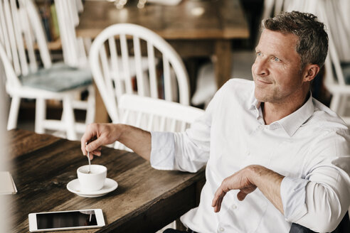 Businessman in cafe drinking coffee, daydreaming - KNSF000026