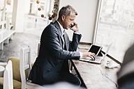 Businessman sitting in cafe, working - KNSF000065