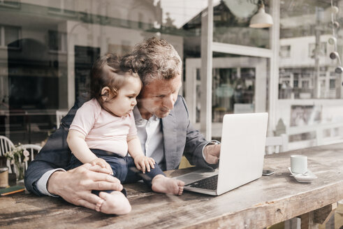 Businessman with little daughter working on laptop in cafe - KNSF000077
