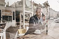 Businessman sitting in cafe, working - KNSF000092