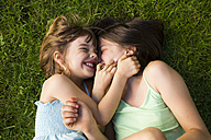Two sisters lying in meadow having fun - LVF005112