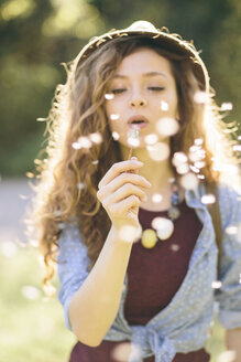 Young woman blowing dandelion - AKNF000058
