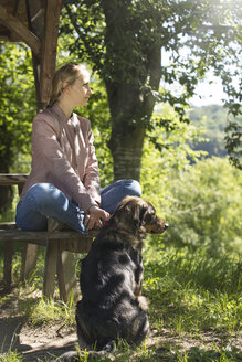 Young woman sitting on wooden bench relaxing with her dog - MIDF000739