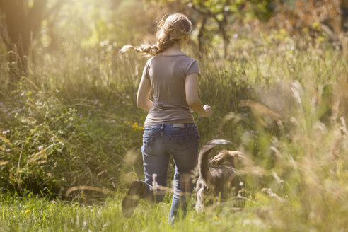 Back view of young woman running after her dog on a meadow - MIDF000745