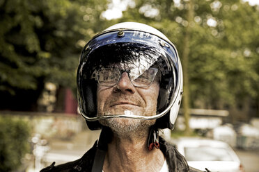 Portrait of smiling biker looking through vizor of his motorcycle helmet - FMKF002750