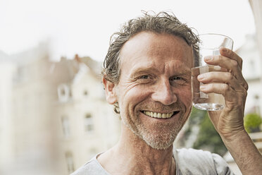 Portrait of smiling man toasting with water glass - FMKF002753