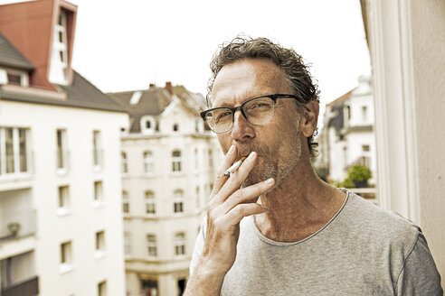 Portrait of man smoking on balcony - FMKF002759