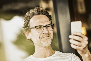 Portrait of smiling man with stubble taking selfie with smartphone - FMKF002768