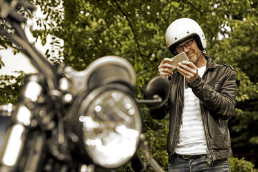 Smiling man with motorcycle helmet taking photo of his motorbike - FMKF002774
