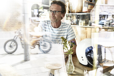 Man sitting behind windowpane of a coffee shop - FMKF002777
