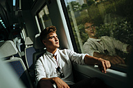 Young man looking out of window on a train - KIJF000542