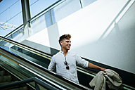 Young man moving down on escalators - KIJF000554