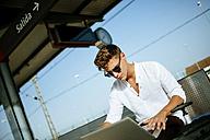 Young man using a laptop at station platform - KIJF000557