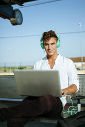 Young man wearing headphones and using a laptop at station platform - KIJF000560