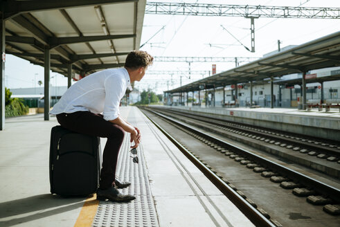 Young man with suitcase waiting at station platform - KIJF000563