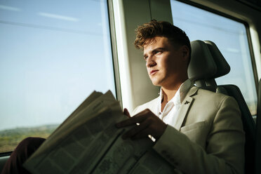Young man reading a newspaper on a train - KIJF000569
