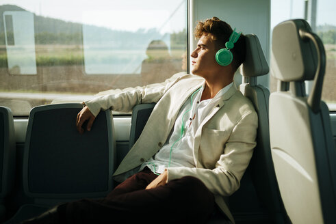 Young man listening to music on a train - KIJF000572