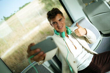 Young man taking a selfie on a train - KIJF000575