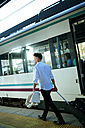 Young man leaving the train at a station - KIJF000578