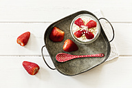 Glass of overnight oats with strawberries on metal tray - EVGF003014