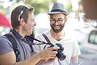 Two happy men with camera outdoors - ZEF008974