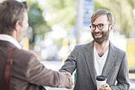 Two men shaking hands outdoors - ZEF008983