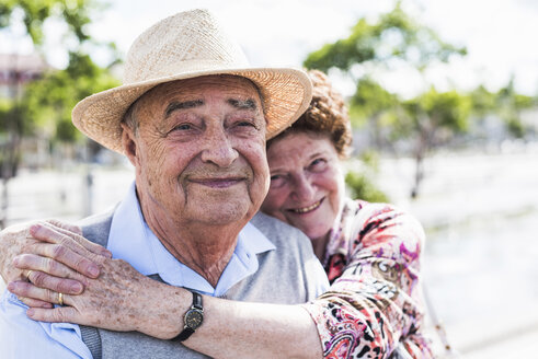 Portrait of happy senior with his smiling wife in the background - UUF008037