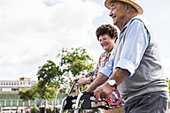Happy senior couple with bicycle and wheeled walker - UUF008046