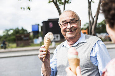 Portrait of happy senior man with ice cream cone looking at his wife - UUF008055