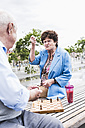 Portrait of senior woman sitting on a bench playing chess with her husband - UUF008070